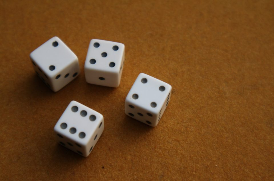 Four traditional dice represent probability in statistics